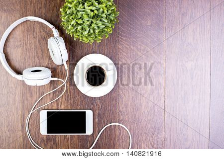 Top view of dark wooden table with blank smartphone headphones coffee cup and decorative plant. Mock up