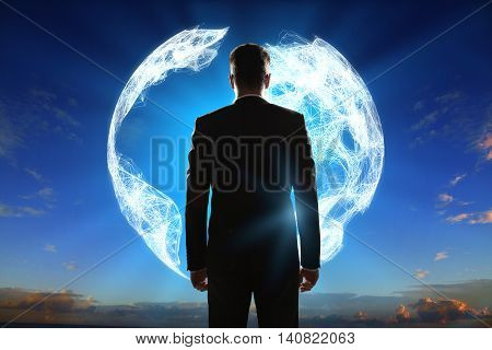 Businessman looking at abstract digital terrestrial globe on sky background. Global business concept