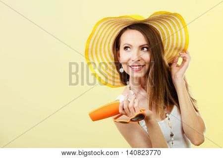 Holidays summer fashion. and skin care concept. Woman in yellow hat holds heart shaped sunglasses sunscreen lotion bright background copy space