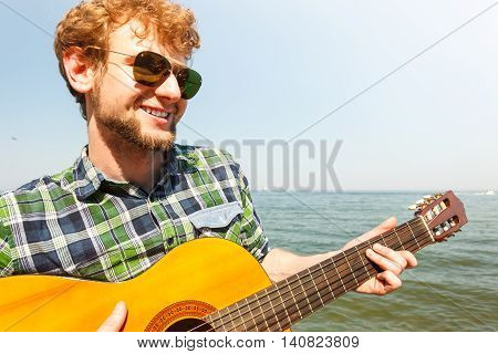 Young man playing guitar. Guy in sunglasses relaxing on summer vacation.