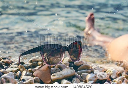 Black mirrored sun glasses on a stones. Shadow from glasses. Sunlight. Summer concept. woman´s leg