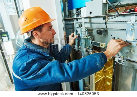 technician worker adjusting elevator mechanism of lift