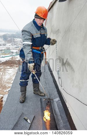 Flat roof installation. Workers melting bitumen roofing felt poster