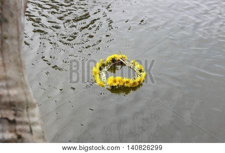 Wreath of yellow dandelions on the water
