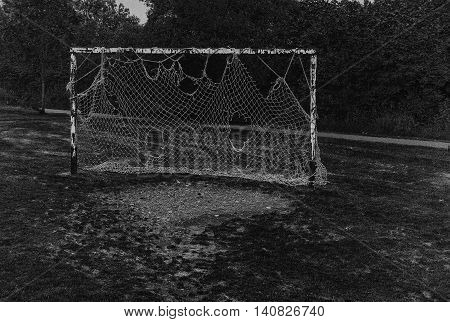 a set of old football goals and net clearly seen better days