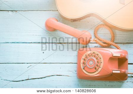 Retro orange-red telephone and the guitar on the old wooden table with copy space for text or your subject in the past