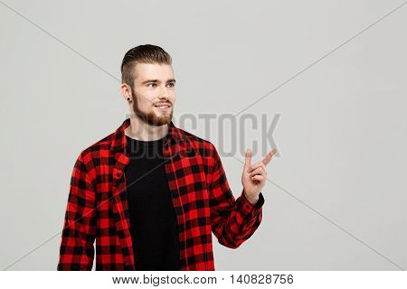 Young handsome man pointing finger in side, smiling over grey background. Copy space.