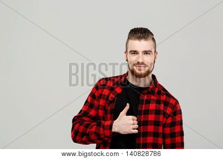 Young handsome man showing okay, smiling, looking at camera over grey background. Copy space.