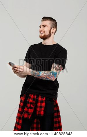 Young handsome man holding phone, looking away smiling over grey background.  Copy space.
