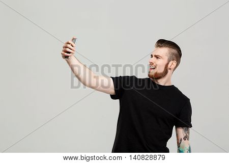 Young handsome man holding  phone making selfie, smiling over grey background.  Copy space.