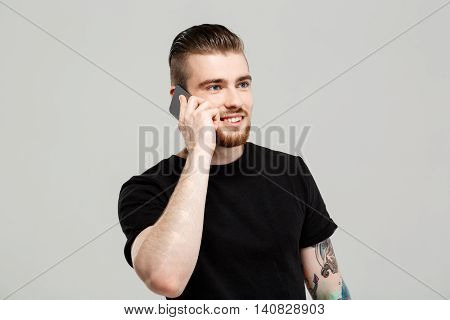 Young handsome man speaking on phone, smiling over grey background. Copy space.