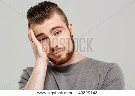 Upset young handsome man posing, looking at camera, hand on head over grey background. Copy space.