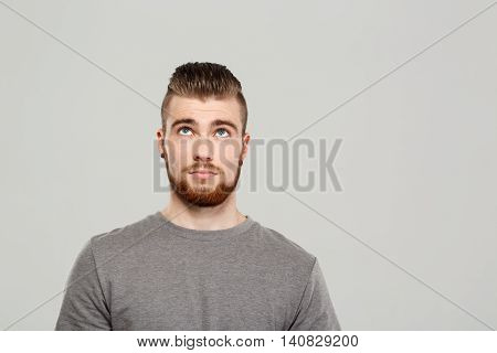 Young handsome man posing, looking up over grey background. Copy space.