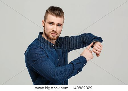 Young successful businessman pointing at watch, looking at camera over grey background. Copy space.