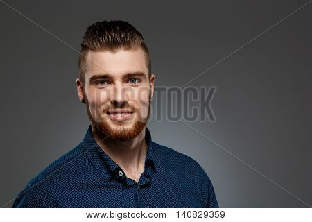 Young successful businessman posing, looking at camera, smiling over dark background. Copy space.