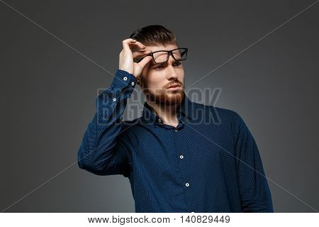 Young successful businessman in glasses posing over dark background. Copy space.