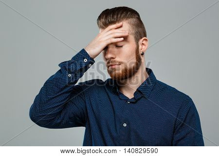 Upset young successful businessman posing, eyes closed, hand on head over grey background. Copy space.