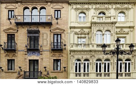 Detail of contiguous buildings with two different classic architectural styles in Seville Spain