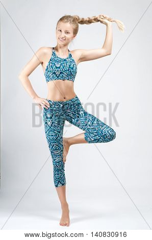 Image of fitness woman in sports clothing. Young woman is practicing yoga