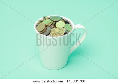 Malaysians Coins In A White Cup With Terquoise Background