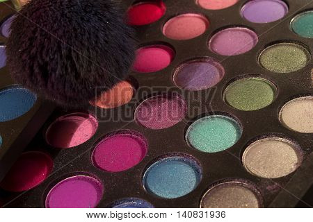 This is a photograph of Eyeshadow Makeup palettes and makeup brushes background