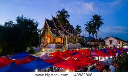 Night market in Luang Prabang, Laos with illuminated temple and sunset sky