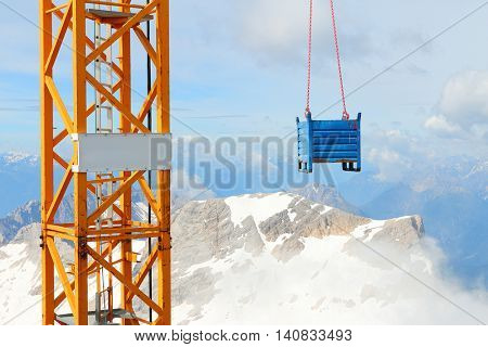 Crane with load on Germany's highest construction site in 2962m. Building the new Zugspitze cable car for tourists and skiers.