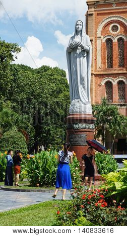 Ho-Chi-Minh-City (former Saigon), Vietnam, 22nd July 2016. Two unidentified young women taking photos of each other in front of a statue at the Notre-Dame-Cathedral. Two other woman looking to the flowers in front of the statue.