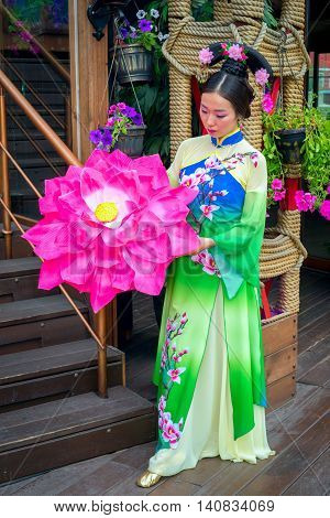 Beautiful Chinese Girl In National Dress With An Umbrella In The Form Of A Flower