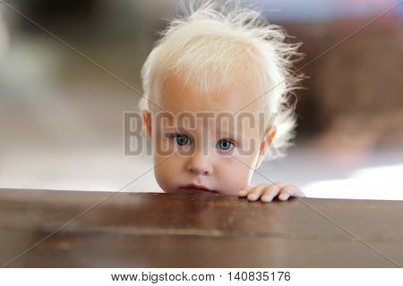 Sad Looking Baby Girl Peeking Over Empty Kitchen Table