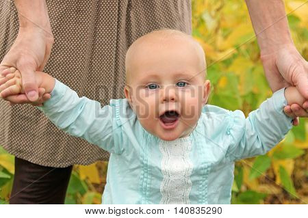 Cute Baby Girl Holding Mothers Hands Walking