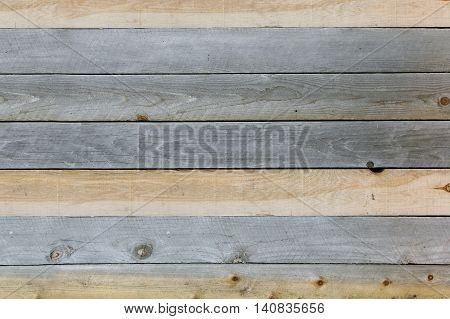 A background of textured rustic wooden plank boards that are knotted and weathered grey and tan brown.