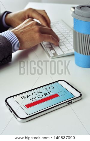 closeup of a smartphone with the text back to work in its screen, on the office desk of a businessman who is typing in the keyboard of his computer