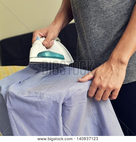 closeup of a young man ironing a striped shirt with an electric iron on an ironing board