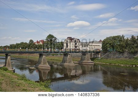 UZHGOROD UKRAINE - AUGUST 3 2015:Pedestrian bridge over the river Uzh in Uzhhorod pconnecting the city with the oldest part of Uzhgorod. There are many tourists always
