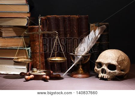 Old brass weight scales near skull and quill on book background