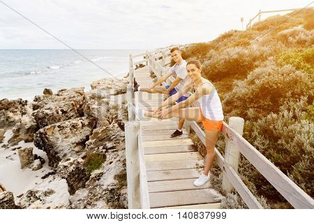 Runners. Young couple exercising and stertching on beach