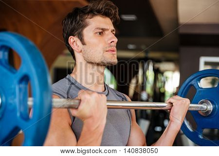 Confident young fitness man doing exercises with barbell in gym