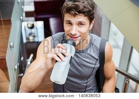 Smiling handsome young man athlete walking and drinking water after training in gym