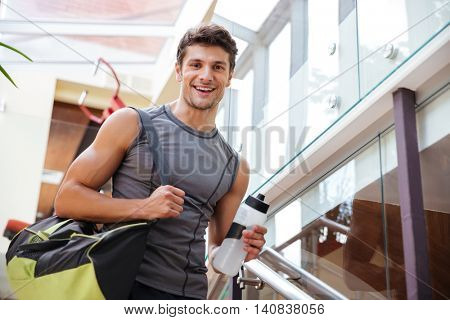 Cheerful young fitness man with bag and bottle of water walking on training in gym