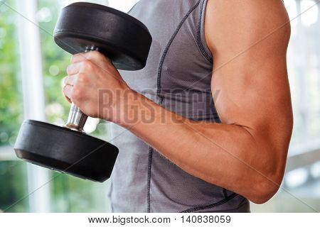 Closeup of athletic young man athlete training using dumbbells in gym