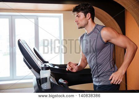 Handsome young man athlete warming up and running in treadmill in gym
