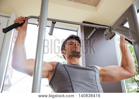 Handsome young fitness man doing exercises for arms muscles in gym