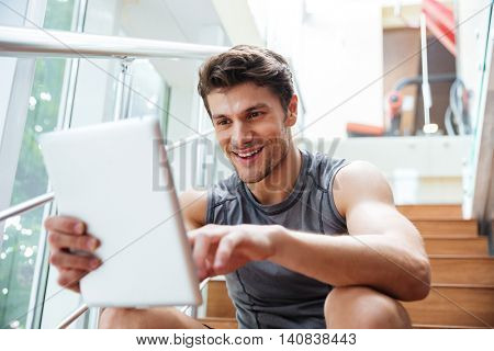 Happy handsome young fitness man using tablet in fitness club