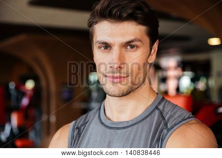Portrait of confident young man athlete in fitness club