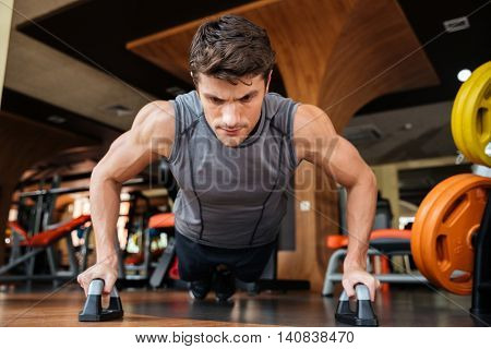 Strong young man athlete training and doing push-ups in gym