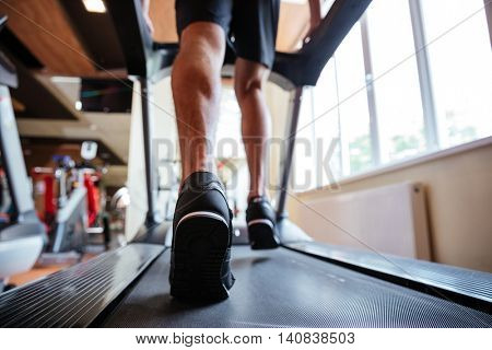 Back view of young sportsman in black sneakers running on treadmill in gym