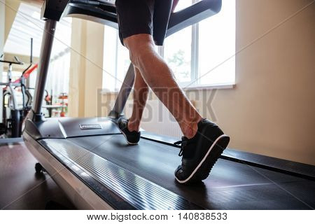 Closeup of legs of young fitness man running on treadmill in gym
