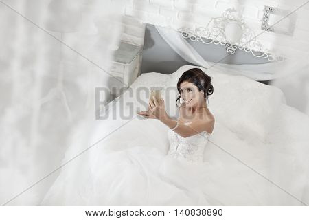 Happy bride making selfie by mobilephone while lying on bed in white bedroom.