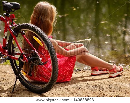 Girl with bicycle. Girl wearing red polka dots dress rides bicycle into park. Girl sits on bicycle on shore river. Sun day.